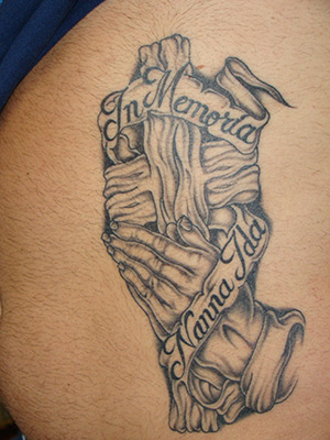 This is a large rib cage belly tattoo featuring a set of praying hands set
