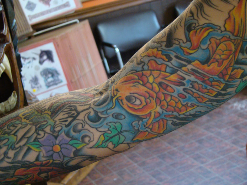 This is an oldschool full sleeve tattoo featuring koi fish, dragons, devils