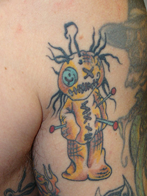 This is a badass voodoo doll tattoo placed on the upper left bicep of the
